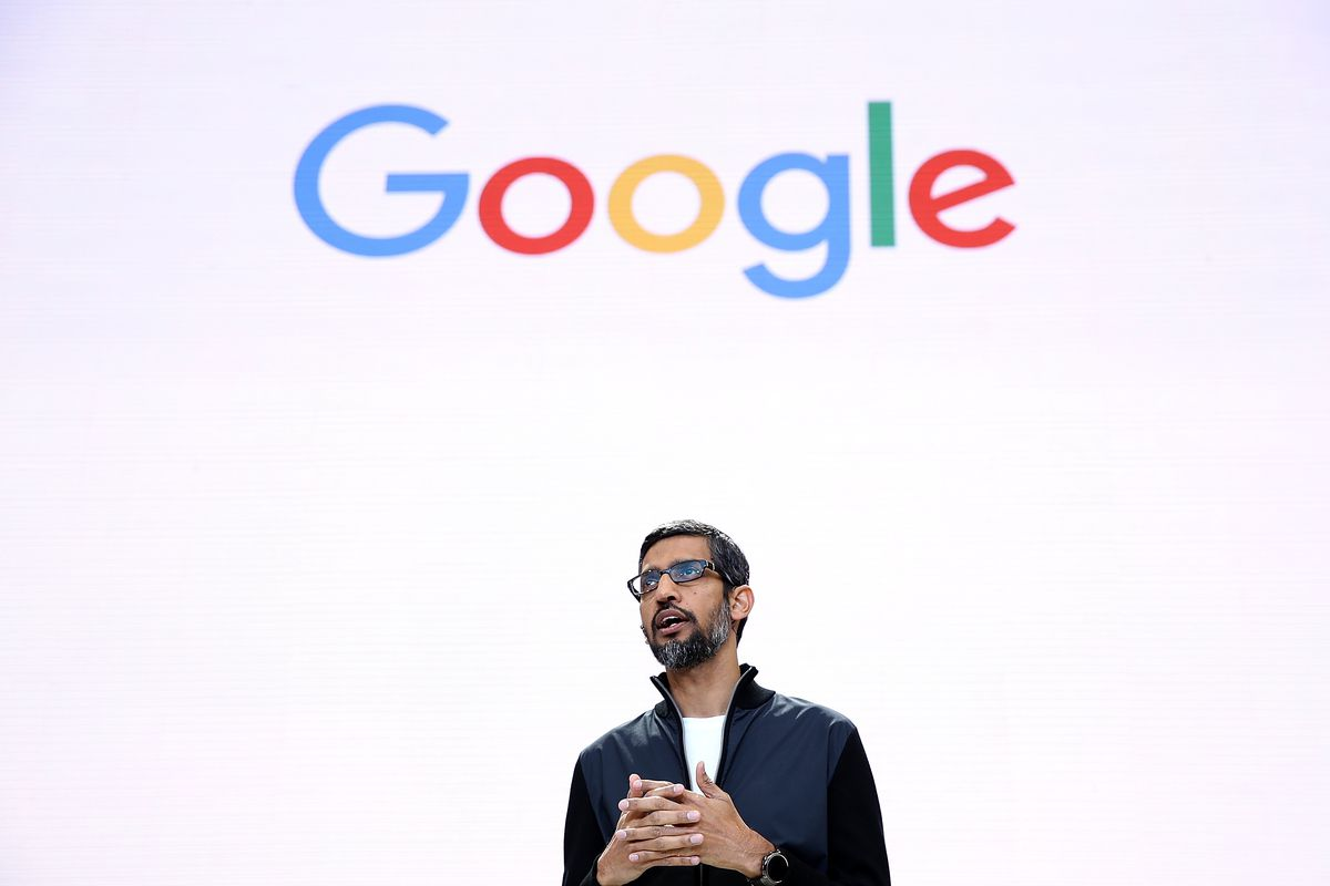 """Google CEO Sundar Pichai onstage in front of a white wall with the word """"Google."""""""
