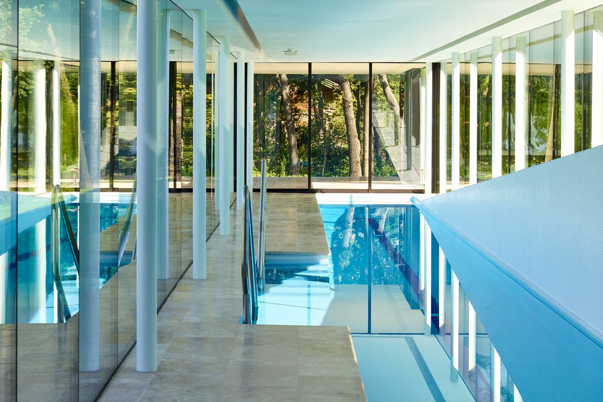 Interior of pool house with glass walls and thin columns.
