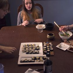Vegan chef Molly Aubuchon, right, eats maki rolls and noodle bowls she prepared with her children, Emma, 13, center, and Sam, 11, left.