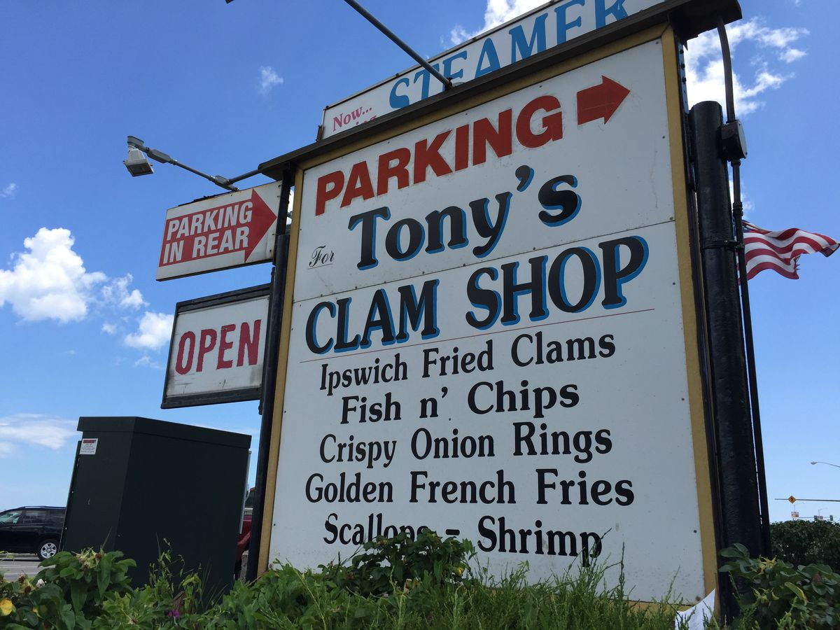 Big white old-fashioned signage for Tony's Clam Shop in Quincy, with a partial menu listed on the sign