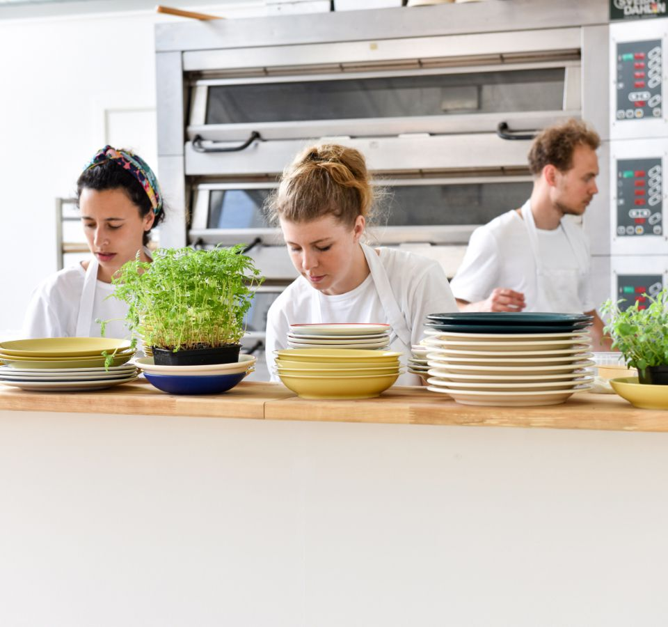 Cooks and bakers prepare unseen dishes behind a high counter stacked with plates and potted plants, in a bright white space with industrial ovens in the background