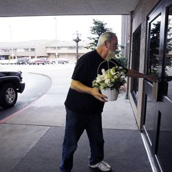Dan Hill delivers flowers at the Life Center Church sanctuary in Tacoma, Wash., Friday, Feb. 10, 2012 in preparation for the memorial for Susan Cox Powell, Charlie Powell and Braden Powell.