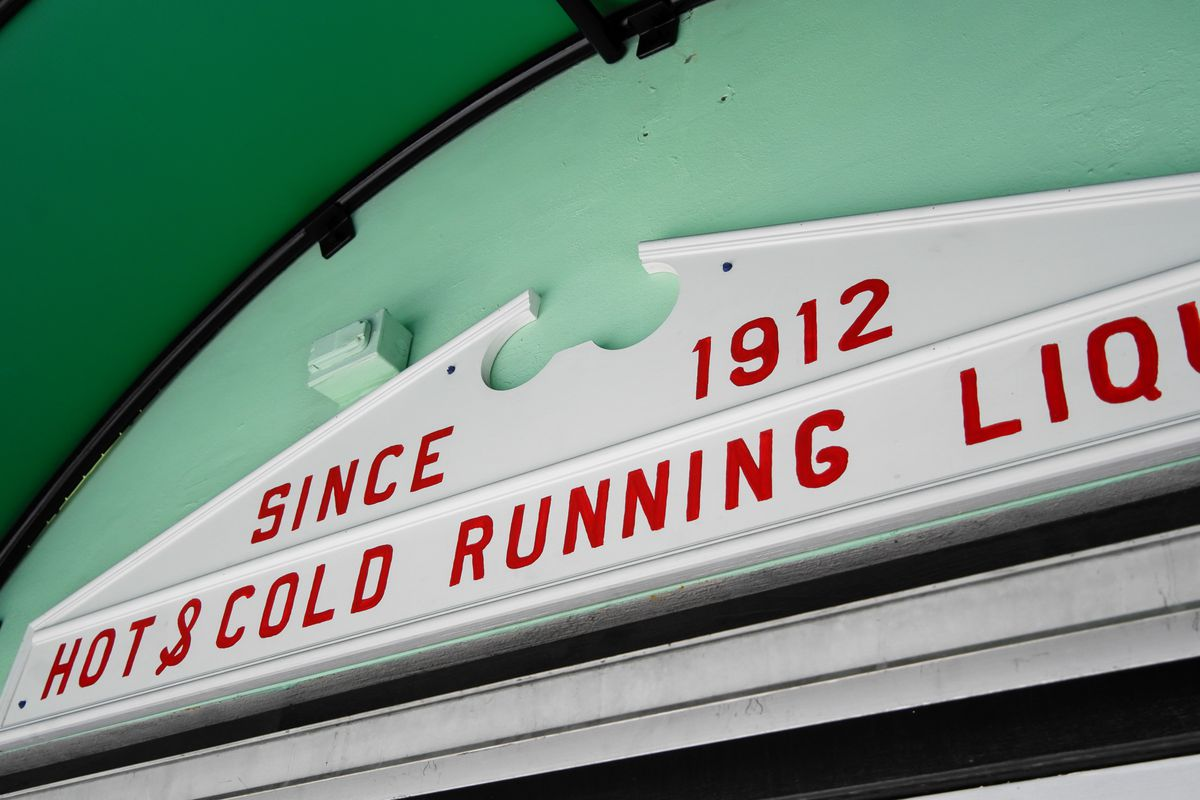 """Close up a white sign that reads """"since 1912 hot & cold running liquor"""""""