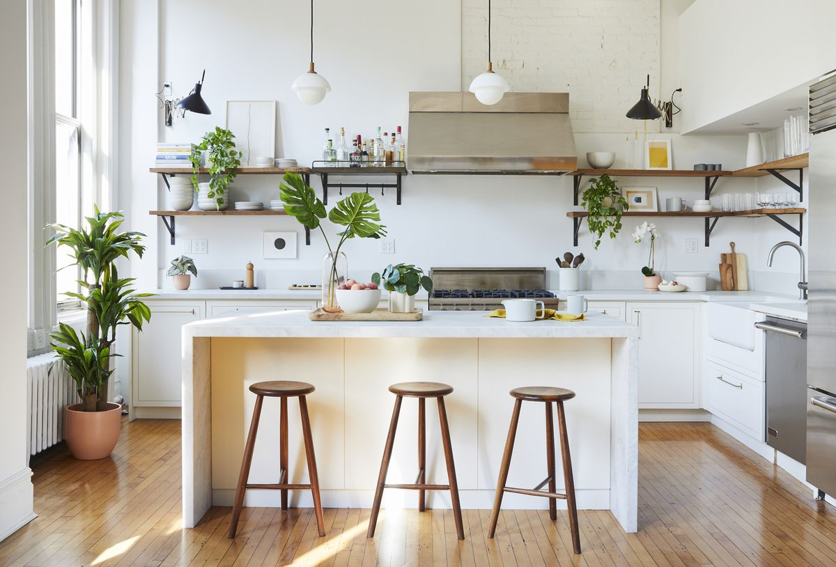 A bright kitchen with white cabinets and kitchen island. Artificial plants in pots are placed on various surfaces.