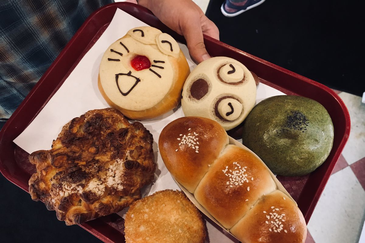 Japanese breads with faces on them on a tray.