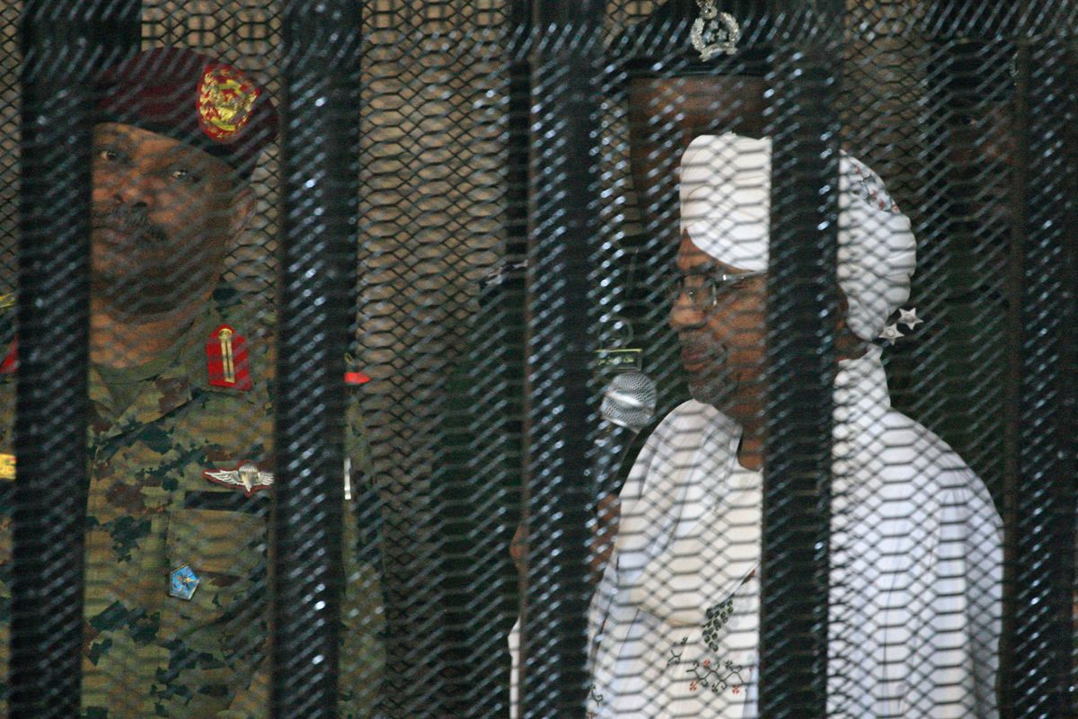 Sudan's deposed ruler Omar al-Bashir, shown behind a security fence and in the company of uniformed guards.
