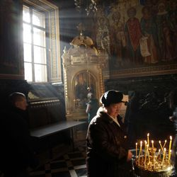 A woman lights prayer candles at the main cathedral in Chisinau, Moldova, during the Epiphany on Jan. 19, 2011.