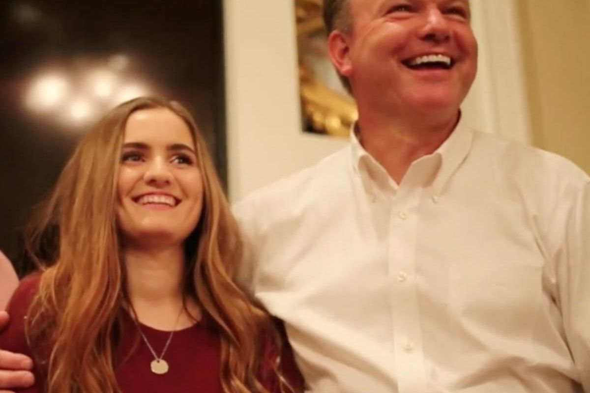 Mckenna Guttery smiles with her father before opening her mission call.