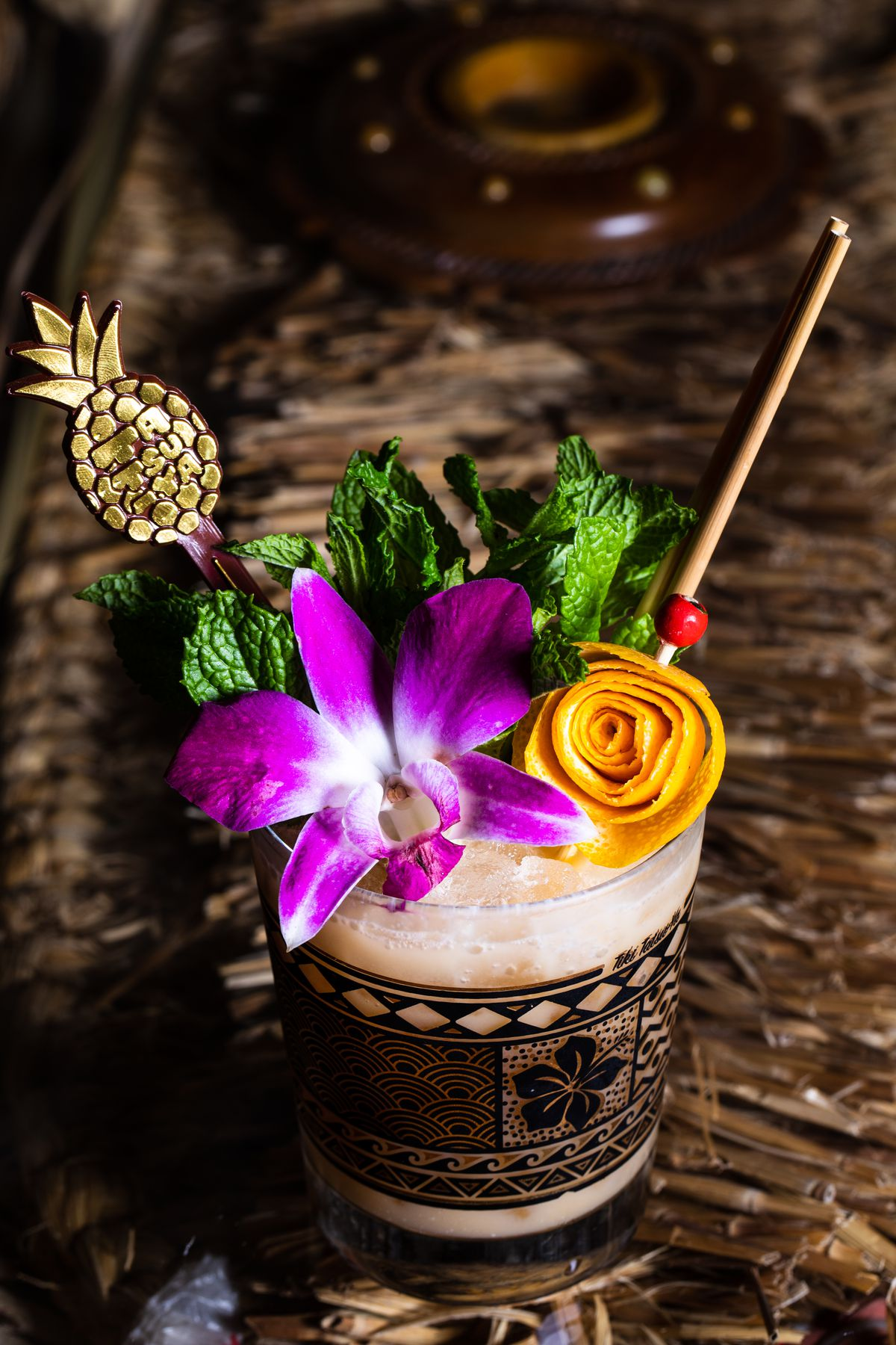 Cocktail topped with an orchid, green mint, and a mango peel curled into a flower, with a pineapple-shaped skewer decoration.