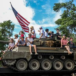 People ride on a tank during the Grand Parade in Provo on Monday, July 5, 2021.
