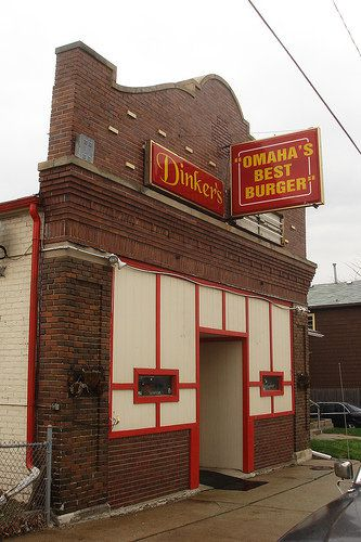 """A red brick Tudor exterior with a sign that reads """"Dinkers"""" and a sign that reads """"Omaha's Best Burger"""""""