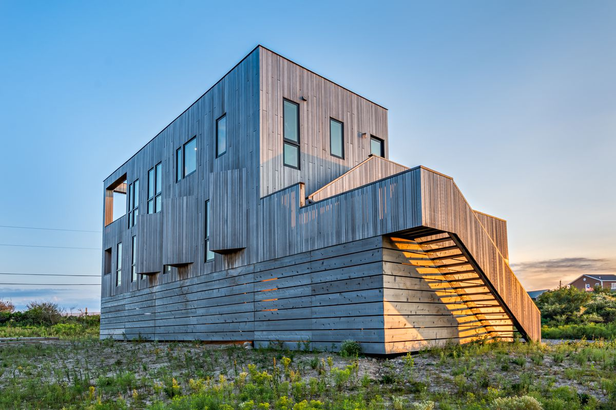An exterior rear view of a boxy contemporary home with wood siding.