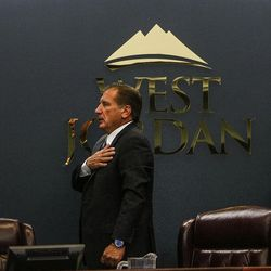 West Jordan City Council members Dirk Burton, left, and Chad Nichols, right, and Mayor Kim Rolfe stand during the Pledge of Allegiance during a City Council meeting at West Jordan City Hall on Wednesday, Aug. 10, 2016.