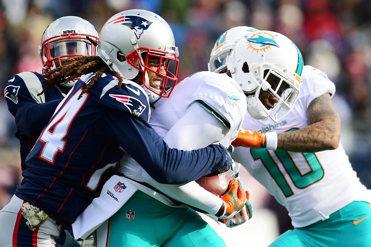 Stephon Gilmore #24 of the New England Patriots tackles DeVante Parker #11 of the Miami Dolphins during the game at Gillette Stadium on November 26, 2017 in Foxboro, Massachusetts.