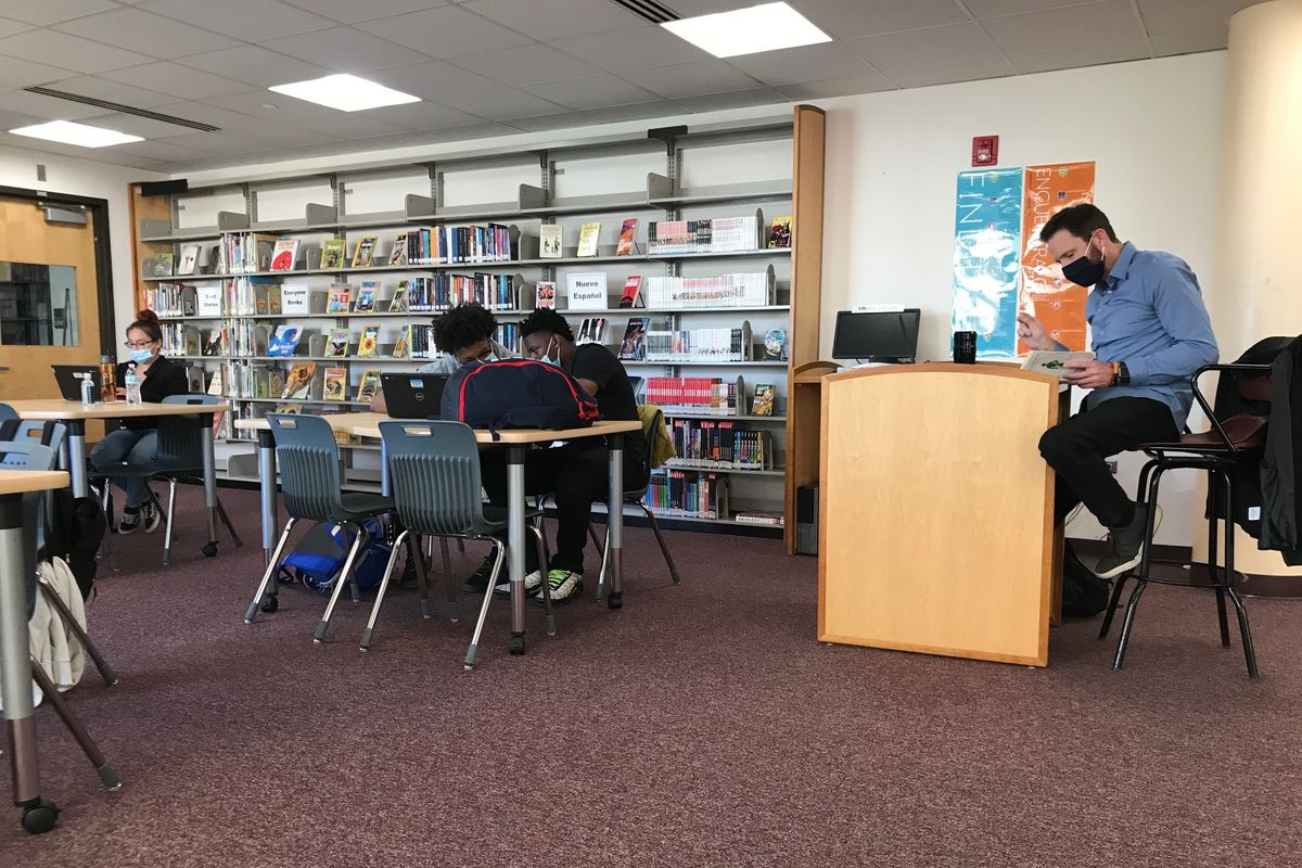 Students and a teacher wearing face masks sit at tables in a high school library during class.