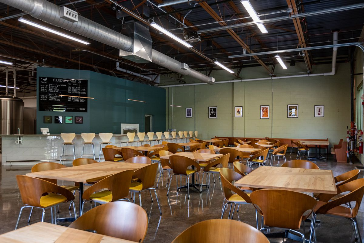 A wide-angle view of Brewery Faisan's taproom shows a light-colored wood furnishings surrounded by light green and blue-gray walls
