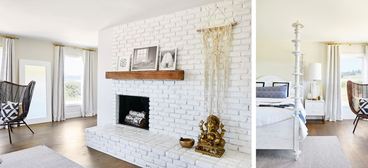 On the left is a room with a white brick wall and a fireplace with logs inside. Artwork hangs on the wall and there are framed photographs on a wooden display shelf. On the right is a bedroom with a large white four poster bed, a chair, and an end-table.