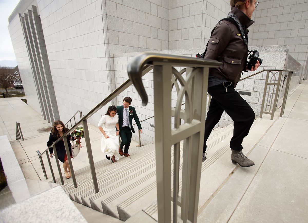 Dan and Tayla Budge, follow their photographer Rebecca Gunnell, of Plaid Pencil Photography up a set of stairs as they enjoy their wedding day at the Draper Temple of The Church of Jesus Christ of Latter-day Saints on Saturday, March 14, 2020. The Wedding had to be moved up two weeks because of COVID-19.