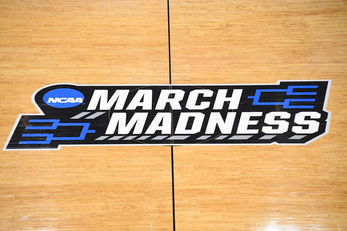 """The center court image for a basketball games that reads """"March Madness."""" There are images of brackets in the upper right and lower left."""
