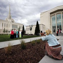 Volunteer Christina Myers takes a photo of the Ward an Seamons families during the Ogden Utah Temple open house, Friday, Aug. 22, 2014.
