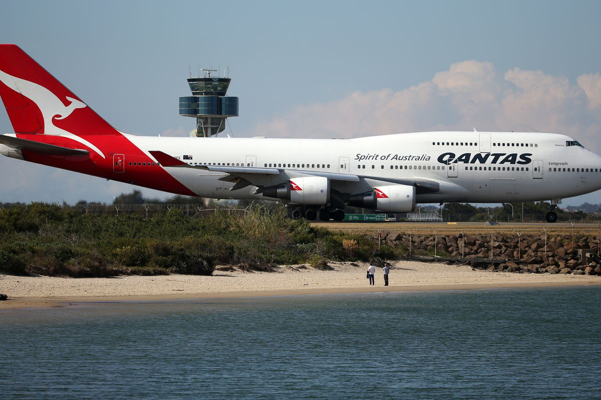 Two people watch from a beach as a Qantas plane taxies on the runway at Sydney Airport in Sydney, Thursday, Aug. 20, 2015.