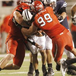 Brigham Young Cougars quarterback Riley Nelson (13) is sacked by Utah Utes defensive tackle Dave Kruger (44) and Utah Utes defensive end Joe Kruger (99)  in Salt Lake City  Sunday, Sept. 16, 2012.