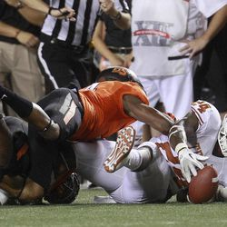 Texas running back Joe Bergeron (24) recovers his own fumble as Oklahoma State cornerback Justin Gilbert (4) reaches for it during the second quarter of an NCAA college football game in Stillwater, Okla., Saturday, Sept. 29, 2012.