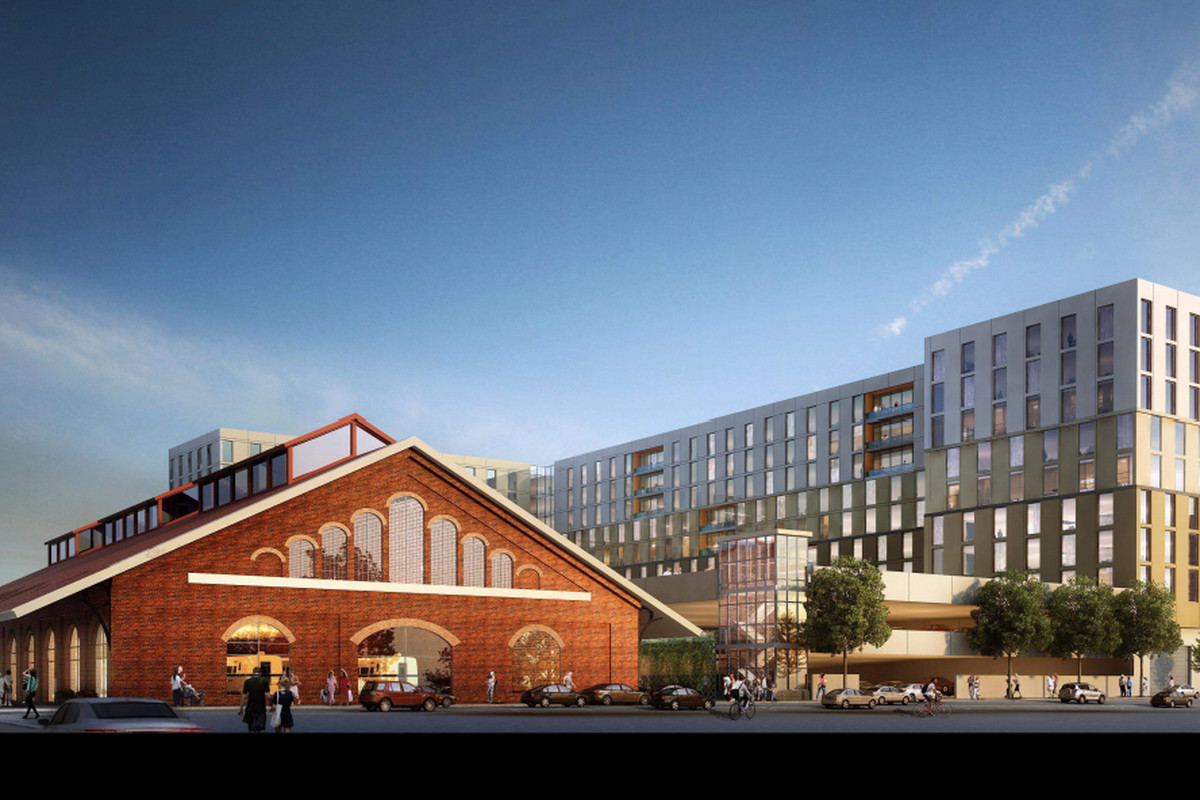 A rendering of a historic red train shed and an 8-story apartment building