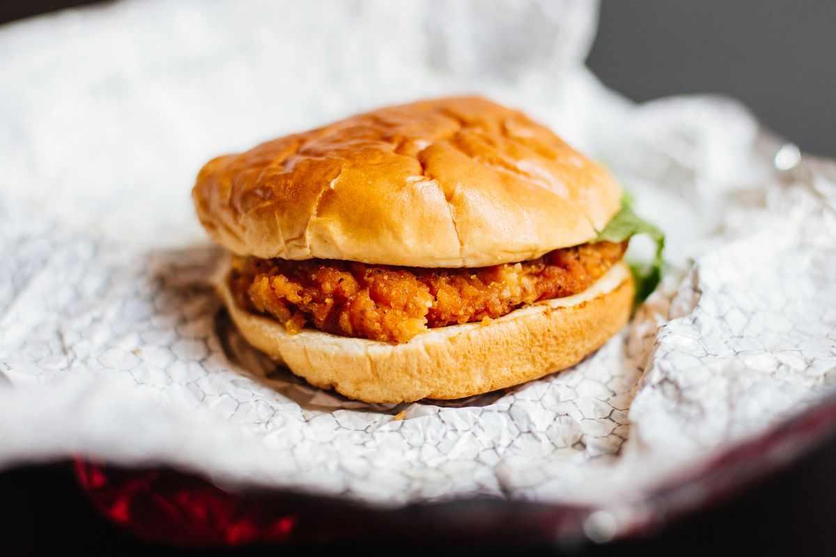 Fried chicken sandwich with salad that sits on a foil wrapper.
