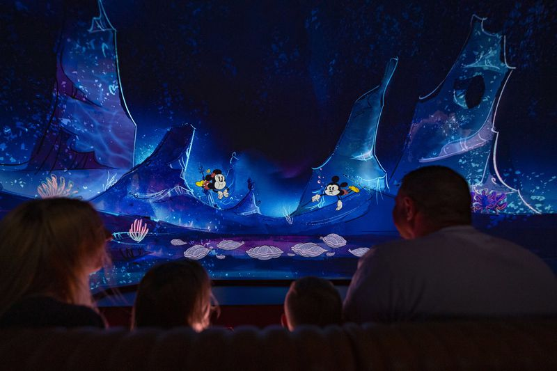 "Guests follow Mickey Mouse and Minnie Mouse underwater as part of their journey through the vibrant world of ""Mickey Mouse"" cartoon shorts in Mickey & Minnie's Runaway Railway"