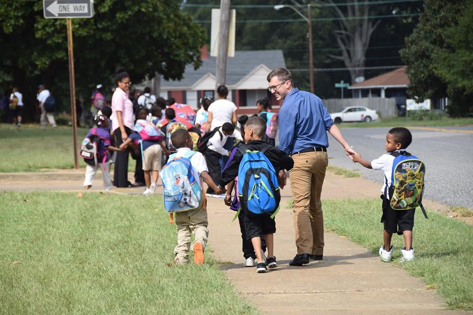 Teacher Carl Schneider walks children home in 2015 as part of the after-school walking program at Whitney Achievement Elementary School in Memphis. This photograph went viral and inspired a First Person reflection from Schneider in 2017.