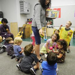 In this April 19, 2012, photo, music teacher Robyn Shippel passes out instruments to a class of 2-year-olds at the Sunshine School in Marietta, Ga. The school is among the first to sign up for a new statewide quality rating system.