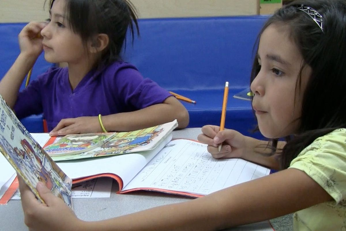 A student in Judy Pansini's advanced kindergarten class at Gust Elementary in southwest Denver fills out her reading log.