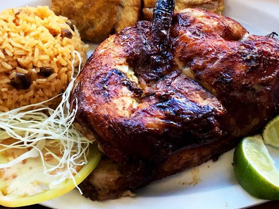 A plate of charred rotisserie chicken with rice, fried plantains, and lime wedges