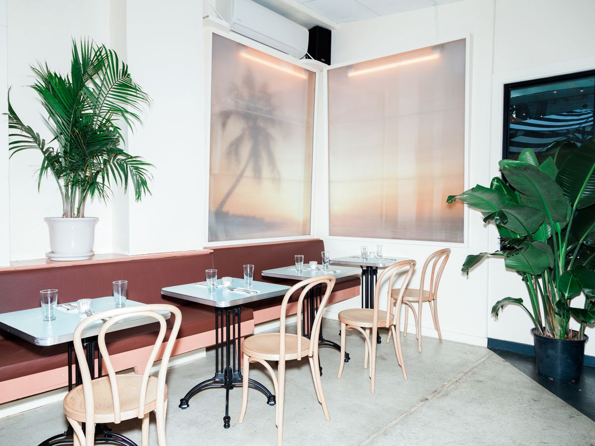 A white-walled dining room with plants and tables and chairs that are set for service.