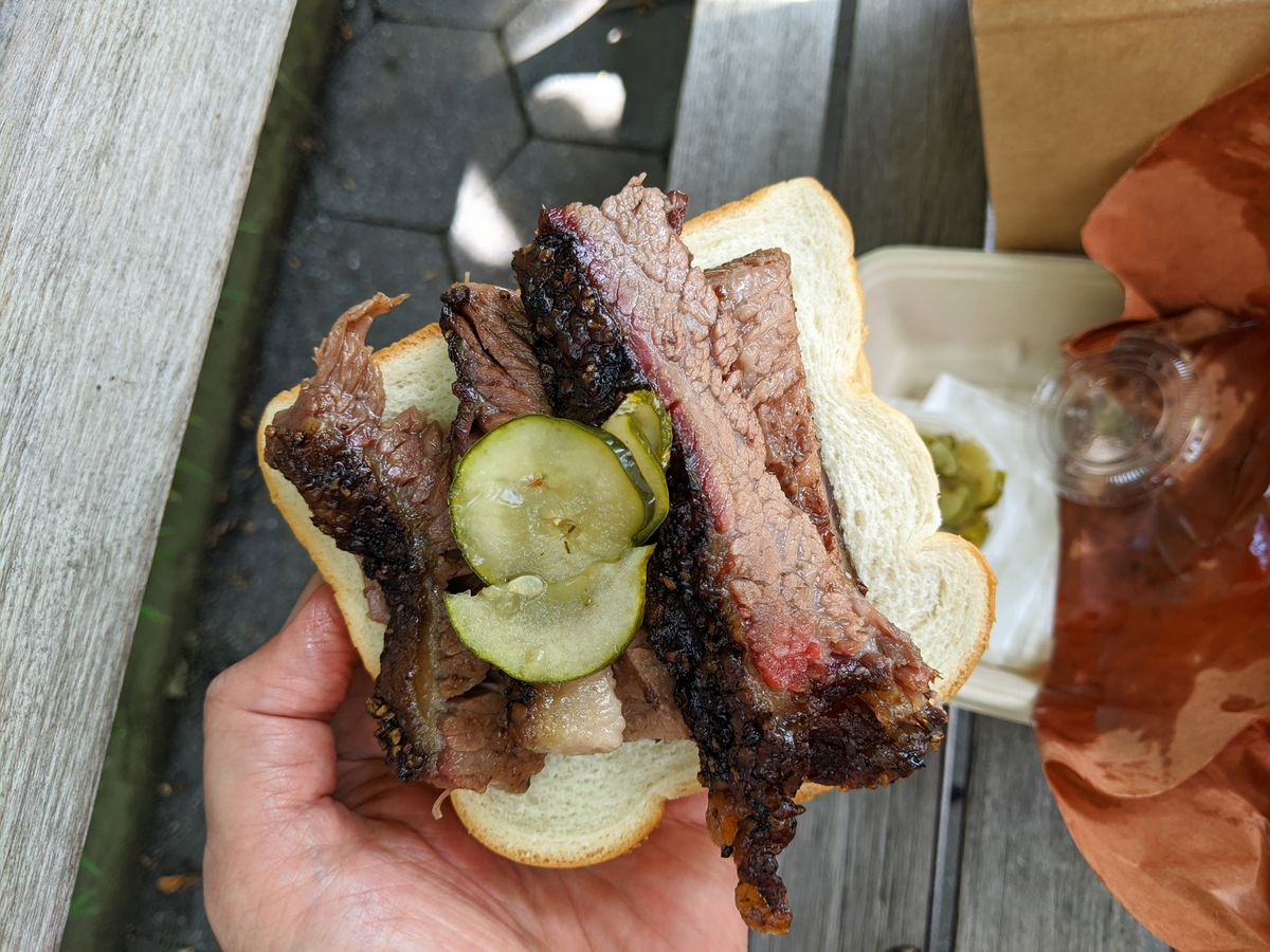 A hand cradles a slice of white bread bent around several slices of blackened beef brisket.