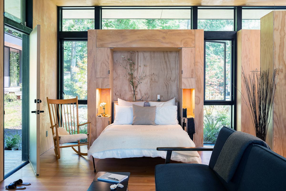 A Murphy bed is pulled down from a wooden module, which is surrounded by glass walls. There is also a sofa and rocking chair in the room.