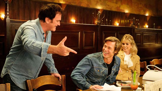 Quentin Tarantino gestures happily as Brad Pitt looks on.