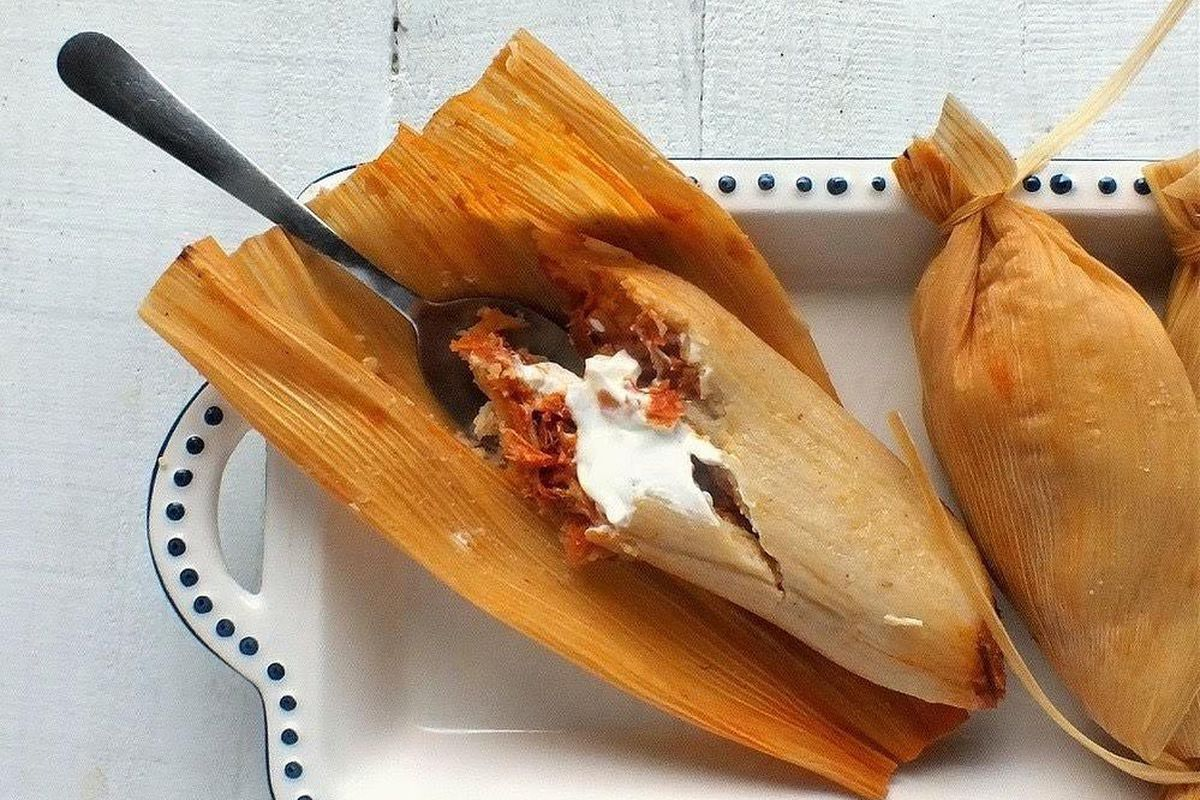 A tamale wrapped in a corn husk with a spoon inside.