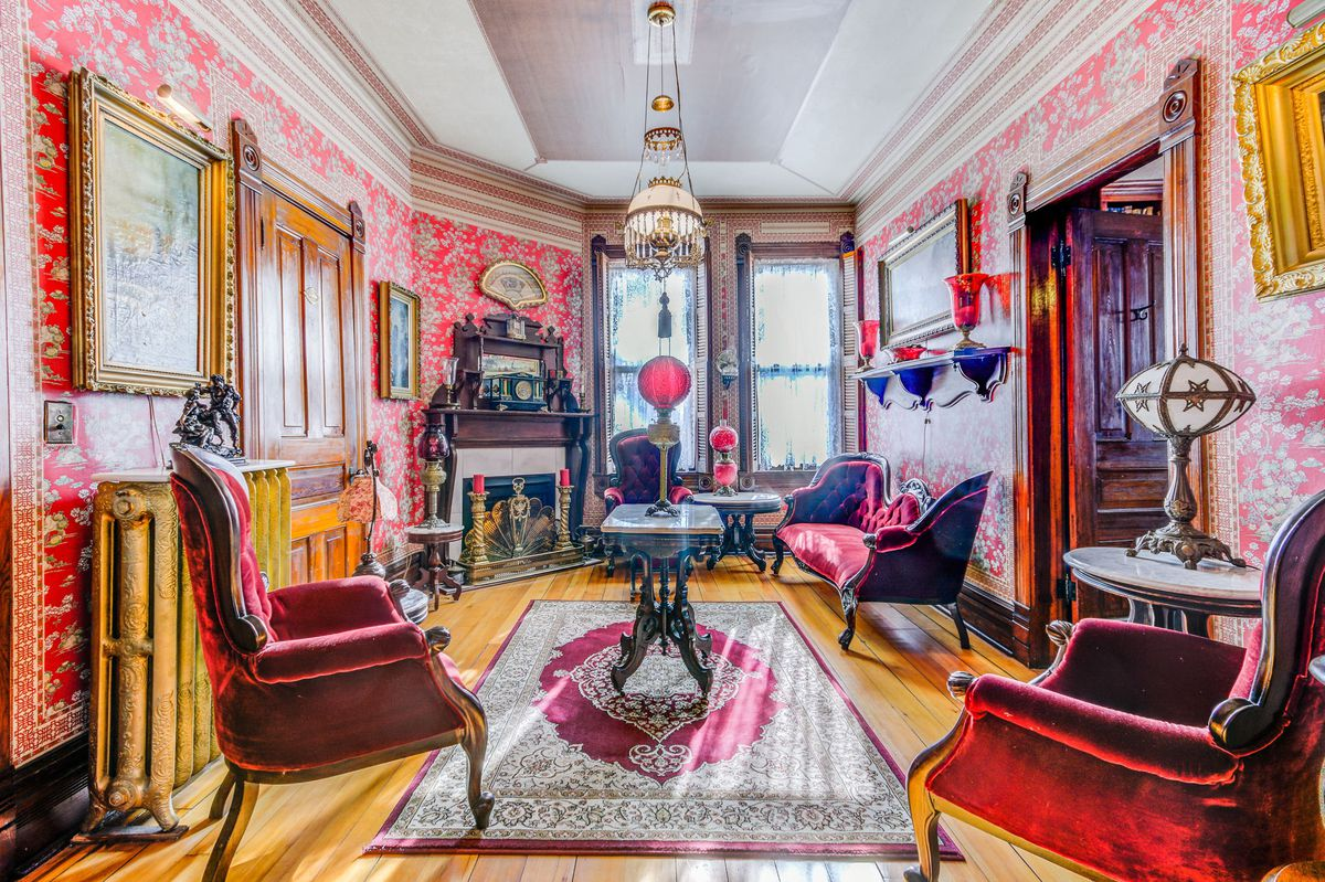 A formal sitting room with a detailed fireplace in one corner, red velvet seating, an Oriental rug, and floral red wallpaper.