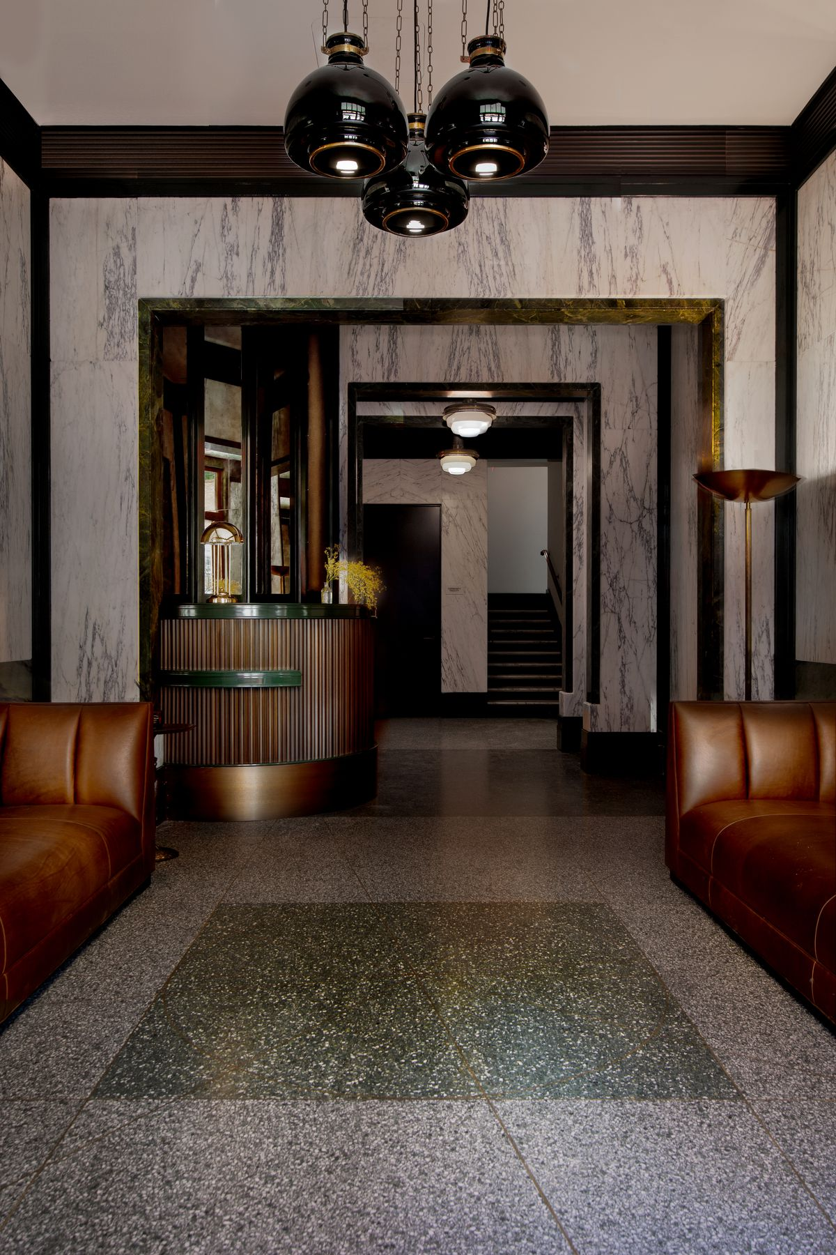 The lobby features marble slab walls and two leather sofas.