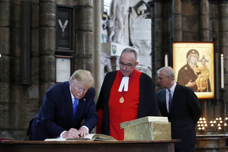 President Donald Trump signs the guestbook at Westminster Abbey with his signature black marker.