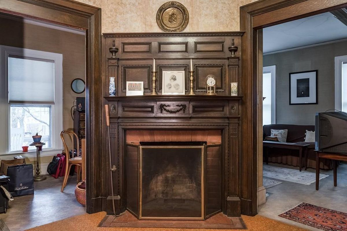A large, carved-wood fireplace in a foyer, with openings into other rooms on either side.