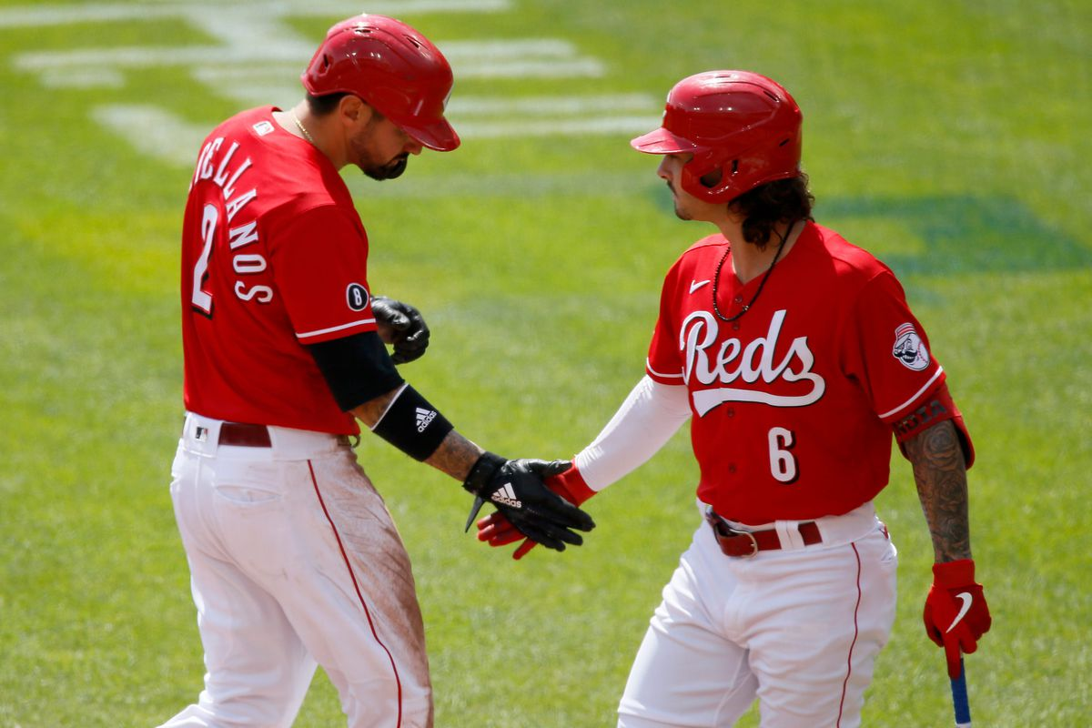 Cincinnati Reds right fielder Nick Castellanos low-fives with second baseman Jonathan India after scoring in the first inning of the MLB National League game between the Cincinnati Reds and the Pittsburgh Pirates at Great American Ball Park in downtown Cincinnati on Wednesday, April 7, 2021. The Reds led 8-0 in the sixth inning.