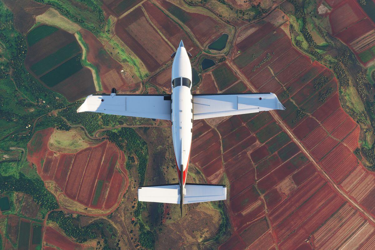 A plane flies over fields of colorful farmland in Microsoft Flight Simulator