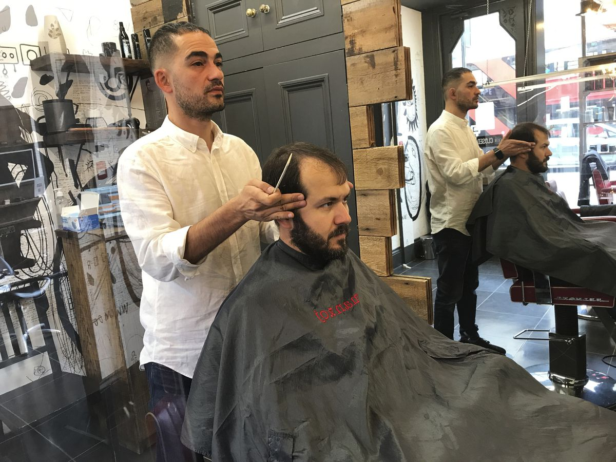 Rado Asatrian cuts a customer's hair at Man-oj hair salon in London's financial district. Before COVID-19, Asatrian usually had 10 to 15 customers a day, but now it's down to three or four.