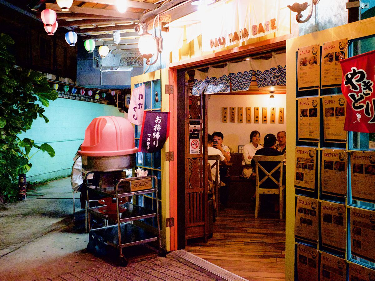A restaurant entrance, decorated with string lights and Japanese signs, with a turquoise alleyway leading away to one side
