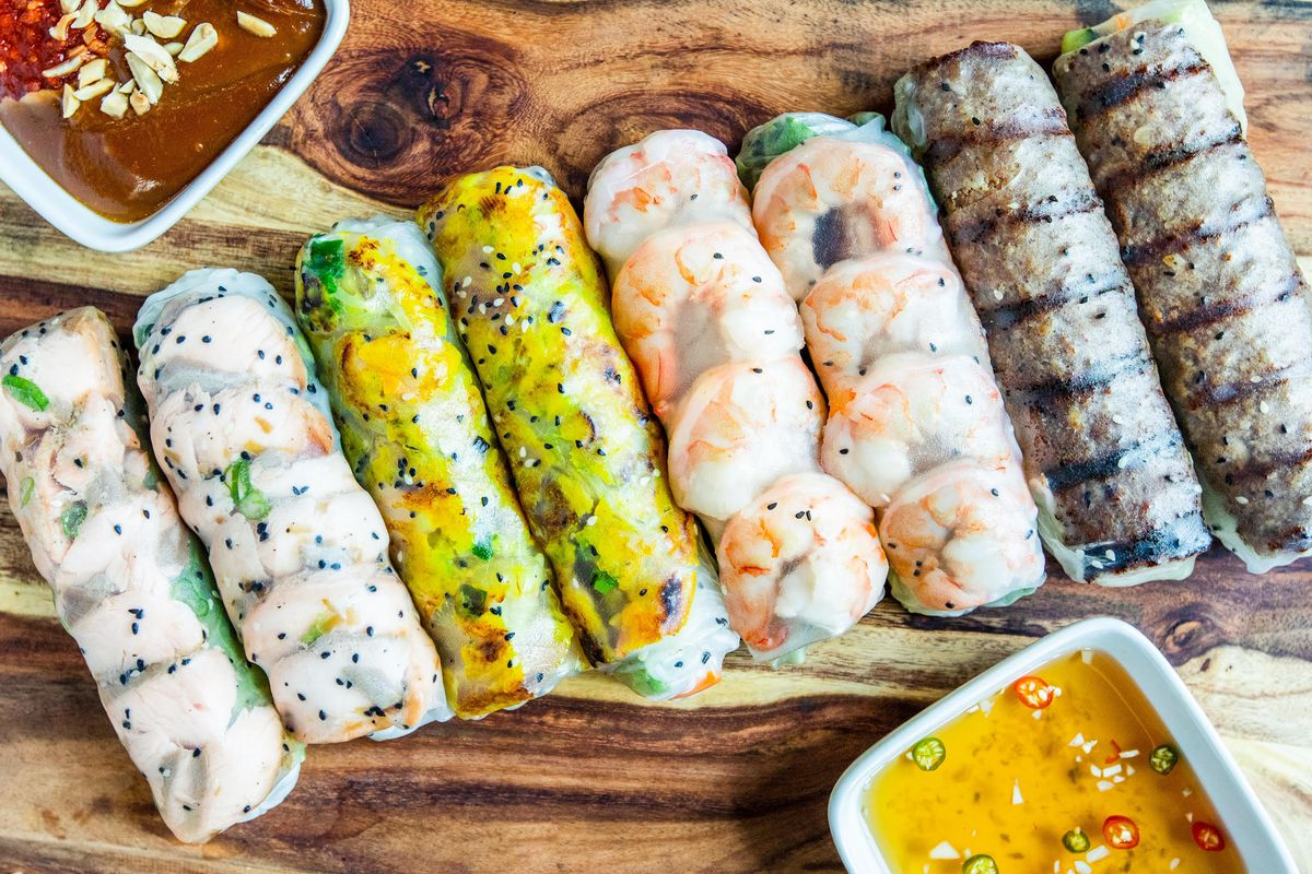 a row of spring rolls on a wooden board filled with chargrilled meat, shrimp and other ingredients. next two the roles are a yellow and red dipping sauce.