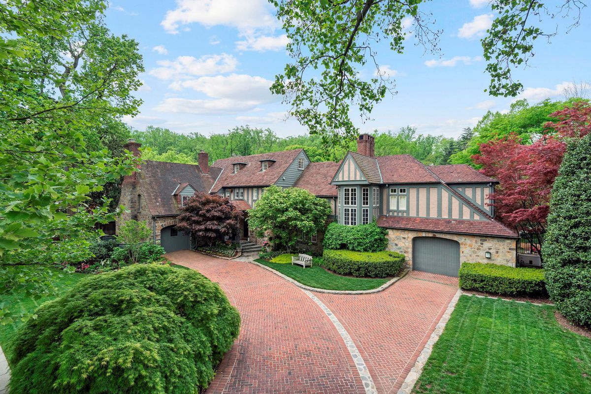 A long brick driveway leads to a historic Tudor house with stone and olive trim.