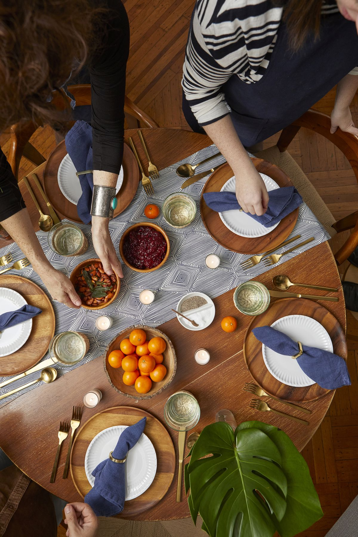 Overhead view of set table, with guests hands in the shot placing down bowls of food on the table.